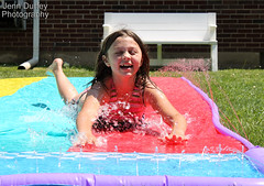 Slip and Slide Fun (Jenn Durfey) Tags: red summer wet water girl fun interesting colorful child belly sprinkler sliding summerfun bathingsuit splashing childplaying playinginthewater watersplashing girlplaying slidingonstomache slipndslide