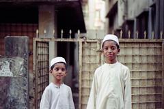 Bonded by Islam... (Sheikh Shahriar Ahmed) Tags: street portrait film kids analog children 50mm kid peace child brothers muslim islam streetlife harmony fujifilm society ahmed sheikh muslimkids nikonf6 shahriar tupi af50mmf18d khilgaon fujicolorc200 epsonv330 sheikhshahriarahmed