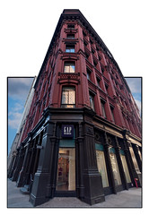 A building on Broadway (Michel Couprie) Tags: street city nyc red urban usa newyork building canon rouge eos town perspective sigma wideangle reflet reflect frame 1020mm rue btiment ville cadre outofbounds oob grandangle 450d