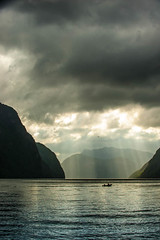 Sun is coming to the fjord (Tommy Hyland) Tags: light sea sunlight mountain seascape nature water glass norway landscape golden coast boat quiet view cloudy calm rowing fjord sunrays distance elongated rowingboat frafjord heavyclouds peoplefishing birduphigh inspiringcreativeminds