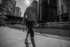 The walk (Adam D Dooley) Tags: city urban woman sun chicago sunglasses illinois downtown cityscape skyscrapers exercise streetphotography scene il ttl chicagoriver waterbottle determination chicagoriverwalk tourthroughalens