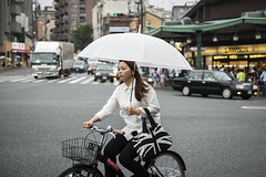 Lone Bike Rider (Igor Voller) Tags: auto street urban woman white black cars girl bike bicycle japan shop lady umbrella kyoto riding  frau unionjack fahrrad  lawson    regenschirm          strase frulein