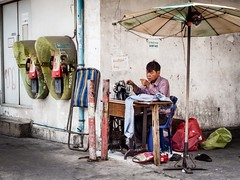 Street tailor (Willfrolic) Tags: street thread umbrella work thailand photography alone sitting sad bangkok sewing working thai thinking tailor motions
