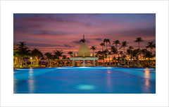 Sunset Poolevard (andyrousephotography) Tags: longexposure sunset sun beach pool bar clouds swimming canon hotel coast warm glow venezuela windy gale aruba 5d oranges reds palmbeach riupalace 24105 dutchcaribbean