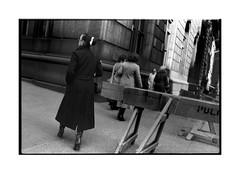 Woman with boots, bun, and barricade (Richard C. Johnson: AKA fishwrapcomix) Tags: newyorkcity blackandwhite bw film monochrome analog manhattan archive 1978 analogue 20thcentury nikonf kodakplusx oldcrap endofempire backpages scanfromnegative nikkor35mm paxamericanus