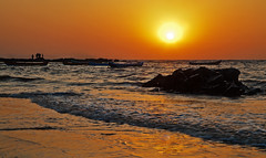 Manori Surf and Sunset (arfabita) Tags: ocean sunset red sea people orange sun playing color beach nature water colors silhouette yellow horizontal set sunrise landscape boats dawn boat fishing globe sand rocks surf waves glow sundown natural dusk sandy horizon relaxing orb tourists rockface boulders hues canoes environment glowing leisure recreation rise enjoying pleasure atplay beautyspot vessels bouncing arabiansea beachcombers horizonline watiching nicescene atleisure