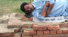 Sirf neend (Raja Islam) Tags: pakistan sleeping man brick relax shoe newspaper sleep bricks poor pillow sheet karachi chappal