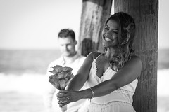 Happiness Defined (haddartist) Tags: ocean wood flowers light portrait sky blackandwhite bw woman white man blur beautiful beauty smile sunshine smiling happy virginia pier wooden couple waves mood afternoon dress photoshoot bokeh background naturallight sunny jewelry monotone tattoos savethedate together oceanside foam pilings bouquet posts virginiabeach photosession oceanfront sandbridge underthepier portraitsession preweddingpics amphotography