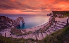 Durdle Door at Sunset (chasingthe_stars) Tags: ocean longexposure pink sunset sea sky orange sun seascape colour beach rock clouds canon landscape seaside arch cove shingle steps smooth dramatic dorset coastline serene iconic circularpolarizer durdledoor jurassiccoast leefilters canon6d leebigstopper
