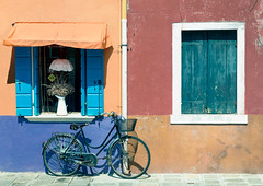 A bicycle does get you there and more.. (areyarey) Tags: street old travel flowers venice summer urban italy orange house color colour window colors bike bicycle architecture facade vintage island italian colorful paint mediterranean basket ride bright transport entrance vivid sunny front journey cycle transportation biking shutters shutter venetian summertime colourful venecia leaning arrangement saddle burano veneto areyarey