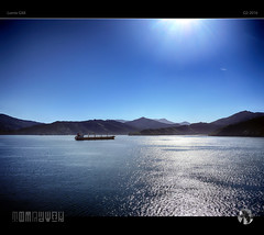 Commerce in Blue (tomraven) Tags: blue light sun water reflections lumix ship glare flare sounds flicker bulkcarrier gx8 tomraven aravenimage q22016