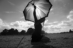 Keeping the sun in the umbrella (rossellanot) Tags: park sky bw woman sunlight nature grass sunshine silhouette dreadlocks clouds contrast umbrella blackwhite arty sunny blackdress blackwoman
