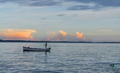 Fisherman at sunset (Elisa.95) Tags: sunset sky italy lake water colors clouds boat fisherman nikon reflexes