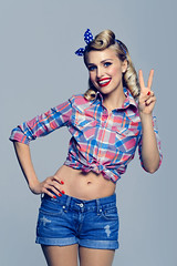 woman, showing two fingers or victory gesture, dressed in pin-up style (xuanlocshop.com) Tags: old 2 two people woman girl up smiling fashion sign female vintage fun happy clothing cool model women 60s funny pin peace fifties hand arm good finger great gesturing hairdo style ukraine victory retro business jeans grooming american 50s positive win emotional gesture hairstyle showing success pinup winning coiffure caucasian successful