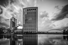 Anadarko Clouds (Mike Schaffner) Tags: longexposure bridge blackandwhite bw lake reflection building tower water monochrome bulb architecture clouds skyscraper reflections us blackwhite woodlands texas arch unitedstates squares curves sunburst hackett anadarko tiltshift thewoodlands lakerobbins canontse24mmf35lii