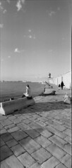 That lonely girl (VALERIA MORRONE  ) Tags: sea bw woman mer lighthouse kids walking children faro reading book mar donna women mare child katy horizon mother libro bn promenade donne valeria lettura ilford puglia molo det piccola leggere apulia monopoli morrone