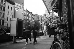 Hidden Beauty (bat0urav3) Tags: street city nyc flowers urban white newyork black flower film monochrome beauty bike booth nikon phone bokeh manhattan soho sharp sidewalk bnw fm2 400asa kentmere filmisnotdead unnotice