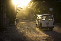 sun catches the dust. (DominicStafford.) Tags: travel light sunset shadow sun sunlight hot dusty car contrast truck 50mm evening movement haze asia cambodia driving ray khmer documentary dry transit van southeast dust siemreap 2013