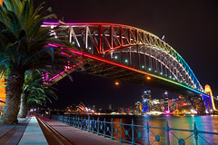 Vivid Harbour Bridge (Kokkai Ng) Tags: internationallandmark placeofinterest sydneyoperahouse operahouse milsonspoint 2013 pier horizontal vividsydney sydneyaustralia multicoloured brightlight australia newsouthwales reflection longexposure bridge sydneyharbourbridge sydneyharbour night black traditionalfestival illuminated light tourism travel winter rainbow dark brightcolour palmtree tree nobody sydney harbour