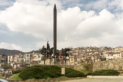 Veliko Tarnovo, Bulgaria (DitchTheMap) Tags: city travel blue houses summer sky sculpture art monument vertical buildings town europe flickr day view hill capital tourist historic bulgaria destination daytime upright picturesque bg easterneurope attraction tarnovo velikotarnovo 2016 veliko
