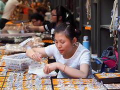 Lunch Time, Panjiayuan Market, Beijing (HerringCoveMike) Tags: china food woman shop booth lunch market eating beijing chopsticks vendor seller panjiayuanmarket