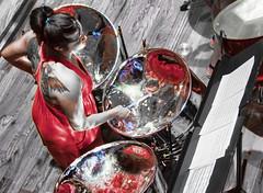A Blinding Performance (Steve Corey) Tags: steeldrumorchestra steelpan performance music cellopans mallets tattoos reddress stevecorey