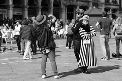 Posing at San Marco (Just Ard) Tags: street venice people blackandwhite bw italy woman white man black blancoynegro monochrome face hat lines sunglasses person photography mono nikon eyecontact noiretblanc zwartwit candid stripes 85mm posing shades d750  biancoenero schwarzundweis justard