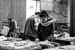 En cherchant un livre (Paolo Pizzimenti) Tags: paris film couple paolo femme olympus f2 12mm f18 fille livre 45mm homme omd argentique em1 doisneau pellicule ravenne penf m43 mirrorless dlicate