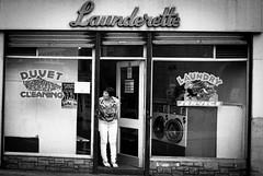 Launderette (forayinto35mm) Tags: blackandwhite london 35mm 50mm minolta streetphotography 50mm14 ilford ilforddelta400 launderette pimlico londonlife delta400 minoltadynax5 blackandwhitefilm ilforddelta laundermat blackandwhiteilford ilfordblackandwhitefilm sonyalpha50mm14 womanbeingnosey