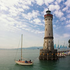 Leaving the harbor of Lindau on the Bodensee (Bn) Tags: blue summer lighthouse lake holiday alps streets tower church colors st swimming germany festive boats island bavaria harbor am fishing topf50 sailing rooftops market speedboat pastel saturday atmosphere lindau landmark panoramic historic marienkirche charming tours rathaus viewpoint bodensee topf100 narrow constance leuchtturm neue openair duitsland bavarian clearwater bayerische watersport dirndl altes peterskirche 100faves 50faves bodenmeer mangturm 33m stephankirche rmerschanze bodenseeradwanderweg lwede