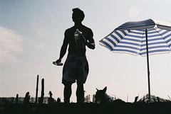 Joseph (onbalcony) Tags: men film beach silhouette umbrella joseph kodak   contaxrx contax50mmf14 kodakcolorplus200