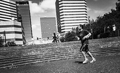 A Good Day For A Run (TMimages PDX) Tags: road street city people urban blackandwhite fountain monochrome skyline buildings portland geotagged photography photo image streetphotography streetscene sidewalk photograph pedestrians pacificnorthwest avenue jogging fitness vignette jogger fineartphotography iphoneography