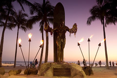 Duke Paoa Kahanamoku (Kokkai Ng) Tags: blue trees sunset people sculpture usa tree male beach sport statue bronze night fire hawaii evening purple waikiki oahu dusk surfer duke surfing garland palm pole palmtree surfboard northamerica honolulu waikikibeach paoa spear puple armsout kahanamoku placeofinterest dukekahanamokustatue hawaiiislands artisticproduct traditionallyhawaiian