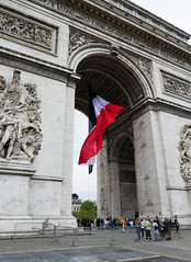 The Arc de Triomphe stands tall above the visitors (Monceau) Tags: paris building architecture tall arcdetriomphe odc frenchflag