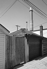 Smokestack (geowelch) Tags: toronto buildings blackwhite garage wires 35mmfilm laneway ilford pentaxmx xp2super400 rogersroad plustekopticfilm7400 pentaxtakumara28mm28