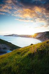 Sunset at Worbarrow Bay (tariqphoto) Tags: ocean uk sunset sea summer england sky seascape green water grass june composite zeiss landscape bay coast landscapes long exposure seascapes angle sony wide dorset coastline a7 jurassic costal 21mm 2016 loxia worbarrow
