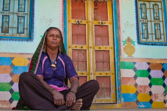 Rabari woman sitting outside of her house. Great Rann of Kutch, Gujarat. India (NeSlaB .) Tags: poverty old travel portrait people woman india house building colors look architecture canon photo necklace women colorful asia village dress desert indian traditional culture photojournalism tribal clothes ornaments earrings tradition tribe ethnic society developingcountries reportage nationalgeographic ethnography rabari ethnology kutch kachchh rann ethnies neslab davidecomelli