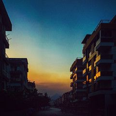 Liman on a hazy summer evening with Foster (Melissa Maples) Tags: cameraphone sunset summer man david apple silhouette buildings turkey square evening asia apartments sundown dusk trkiye 11 antalya iphone liman  iphone6 instagram