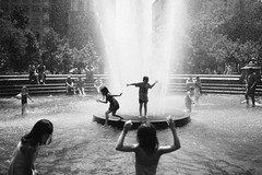 Watery Flow (Dj Poe) Tags: park street city nyc newyorkcity people blackandwhite bw cinema playing ny newyork streets kids zeiss 35mm children photography availablelight manhattan candid washingtonsquarepark sony streetphotography cinematic sprinklers ze 2016 carlzeisslenses vsco distagont1435 djpoe andrewmohrer sonya7rii a7rii sonyilce7rm2 sonya7r2