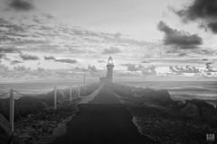 Salt Air (BAN - photography) Tags: ocean light sea lighthouse composite clouds blackwhite rocks monotone chainlink posts pathway rockwall saltspray seawaywall