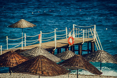 My old pier (Melissa Maples) Tags: blue sea brown beach water turkey pier dock nikon asia mediterranean trkiye antalya nikkor umbrellas vr afs  18200mm  f3556g  18200mmf3556g d5100 konyaaltbeach