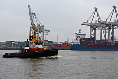 A Tug passing cranes lifting cargo in Hamburg Port, Germany (travelmag.com) Tags: port germany deutschland boat hamburg cargo cranes tug