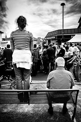 Standing room only. (Mister G.C.) Tags: blackandwhite bw image streetshot streetphotography candid photograph people unposed monochrome urban town city man woman bench seat standing sitting opposite juxtaposition gritty grunge frombehind zonefocus zonefocusing snapfocus ricoh ricohgr pointshoot mistergc schwarzweiss strassenfotografie niedersachsen lowersaxony deutschland europe