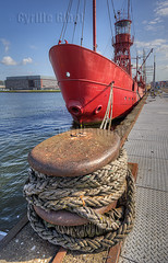 Detail view of anchor post with an old boat of a fire brigade in the background, Amsterdam, the Netherlands (Cyrille Gibot) Tags: color colour netherlands amsterdam vertical closeup port docks outdoors harbor dock iron ship post harbour rusty vessel rope anchor nautical bollard moored