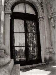 REFLECTIONS OF THE PAST (Sheba53) Tags: door trees windows reflection tree window reflections doorway curtains column mansion windowpane windowreflection windowpanes newportri windowreflections blackandwhiteimage sheercurtains thebreakersmansion