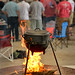 Campfire beans cook over an open flame as camp attendees discuss smokers.