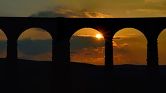 Through the middle (images@twiston) Tags: park morning sky orange sun grass silhouette yellow clouds sunrise landscape dawn golden arch farm yorkshire centre main central silhouettes railway arches farmland line viaduct national fields 24 jericho moor carlisle sebastopol silhouetted northyorkshire midland starburst dales moorland settle 3peaks 1875 ribbleheadviaduct ribblehead stupidoclock scheduledancientmonument belgravia ribblesdale settlecarlisle yorkshiredalesnationalpark yorkshire3peaks battymoss throughthemiddle battywifehole