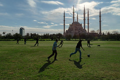 The football game. (RKAMARI) Tags: park street sky game boys weather football shadows sunny mosque daytime adana ~what ~timeofday ~attribute ~structuresarchitecture ~sports ~naturalphenomenon