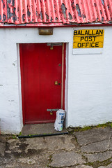 Baile Ailein 4 / Balallan 4, Eilean Ledhais, Isle of Lewis. (soilse) Tags: trees sea house holiday signs building history archaeology grass sport shop architecture mailbox rural advertising landscape islands scotland newspaper ancienthistory postoffice august flags atlantic reddoor hills postbox locks cocacola railing generalstore bog atlanticocean bins chimneys newsagent greysky postalservice satellitedish roadway padlocks tobaconist outerhebrides redroof chimneypots ruralpostoffice flagstones gaidhlig lnasa atlanticislands islandculture corrugatedironroof 2013 corrugatedroof thewesternisles anghaeltacht albain oilein innsegall ruralscotland august2013 balallanpostoffice gaeltachtnahalban lnasa2013 outerhebridesislands scottishgaeltacht thewesternislesofscotland oifigpoistbhaileailein