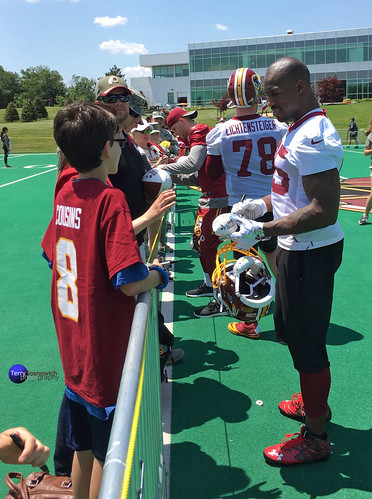Former Terp, TE Vernon Davis signs autographs as a Redskin on opening day of OTAs along with other players.